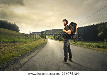 Man with a backpack ready to walk a long road - stock photo