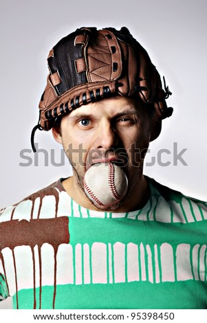 Man with a baseball in mouth and a glove on his head - stock photo
