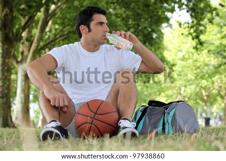 Man with a basketball and bottle of water - stock photo