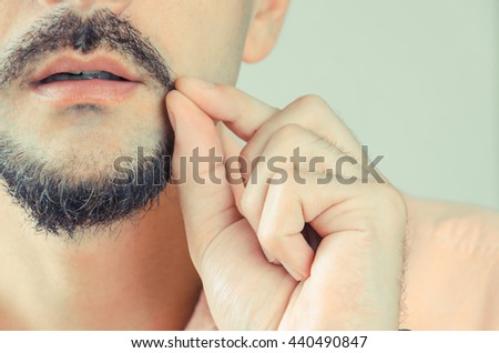 man with a beard and mustache shows and pulls the ends