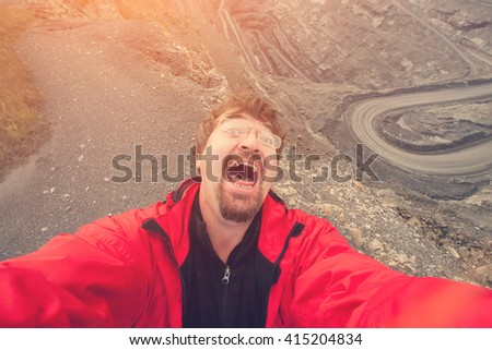 Man with a beard in a red jacket and glasses falls on stones and frightened shouts - stock photo