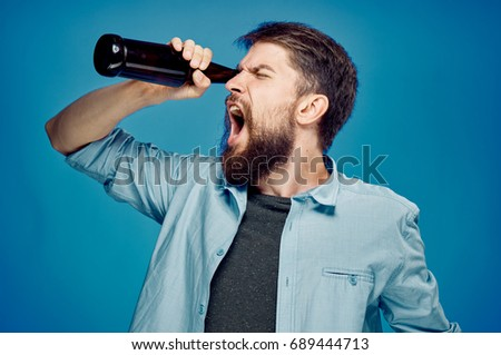 Man with a beard on a blue background drinking beer, alcohol.