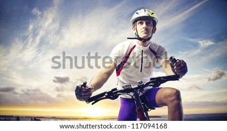 Man with a bicycle on a sunset - stock photo