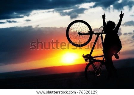 Man with a bicycle on sunset background - stock photo