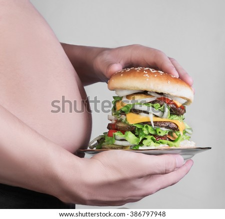 Man with a big fat belly cuddle and holding a plate with a high cheeseburger