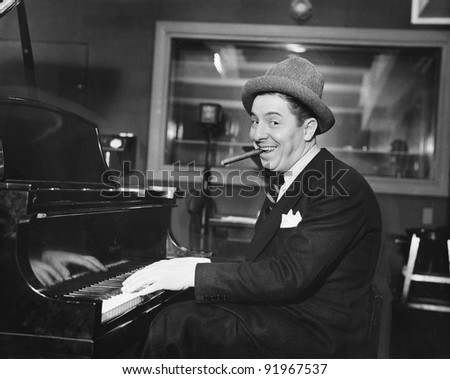 Man with a big smile and a cigar in his mouth playing the piano - stock photo