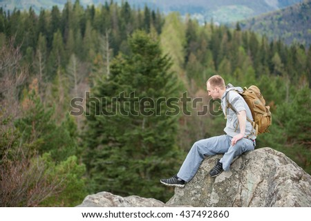 Man with a brown backpack sitting on the peak of rock and looking down on the blurred background of forest valley and hills. Spring nature.