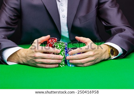 Man with a bunch of chips. Green casino table - stock photo
