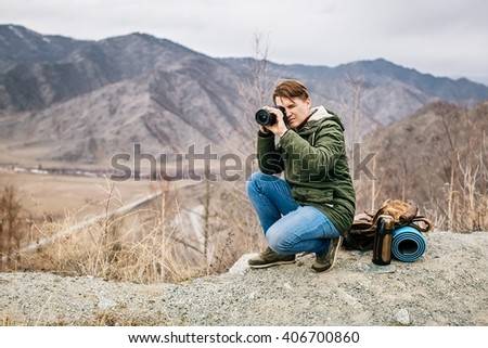 man with a camera on the background of mountains - stock photo