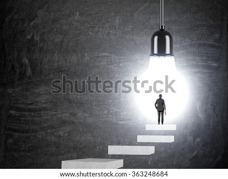 Man with a case standing on a step in front of a huge light bulb, Back view. Black background. Concept of having an idea. - stock photo