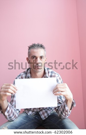 man with a checked shirt holding a blank billboard