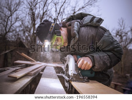 Man with a circular saw sawing plywood. - stock photo