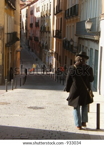 man with a coat walking down a street in Madrid. Spain