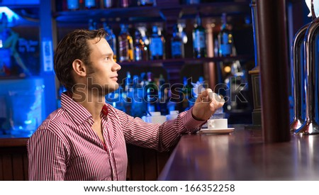 man with a cup of coffee at the bar