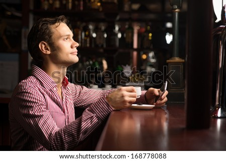 man with a cup of coffee at the bar - stock photo