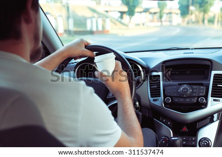 Man with a cup of coffee while driving. don't sleep and drive