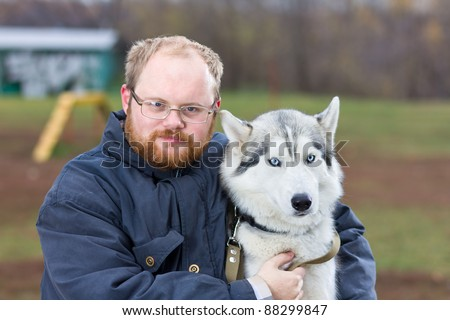 Man with a dog breed Siberian Husky