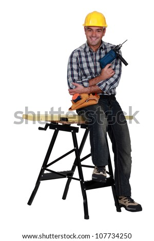 Man with a drill and workbench - stock photo