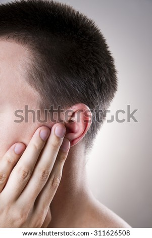 Man with a earache. Pain in the human body on a gray background - stock photo