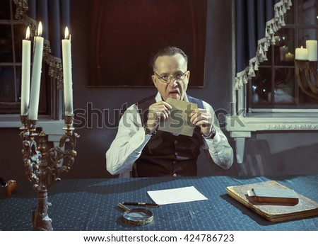 Man with a envelope in hands at the table in his study