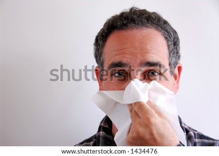 Man with a flu blowing his nose