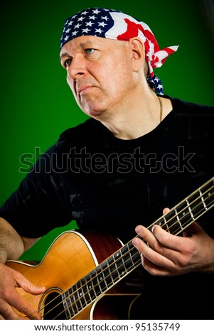 man with a guitar on a green background