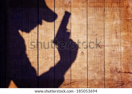 Man with a gun in shadow on a wooden background. You can see more silhouettes and shadows on my page. - stock photo