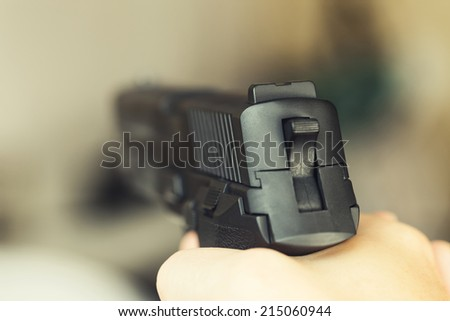 Man with a gun ready to shoot - focus on the back part of gun - stock photo