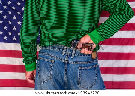 Man with a hand on a  gun in the back of his jeans standing in front of a US flag - stock photo