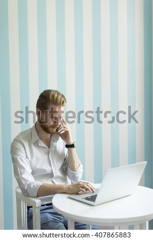 Man with a laptop and a phone at home