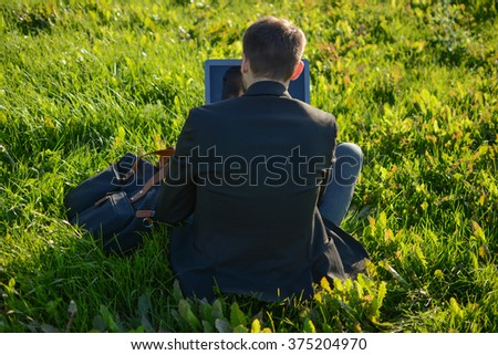 Man with a laptop is sitting on the grass back to us