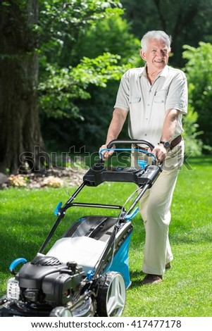 Man with a lawn mower in beautiful green garden