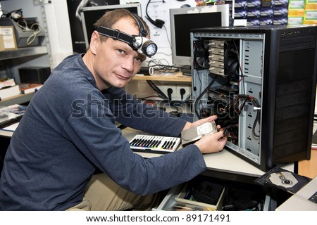 Man with a LED light on his head, working on a desk top computer in a computer repair shop - stock photo