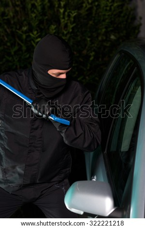Man with a mask and breaking tool trying to steal a car. - stock photo