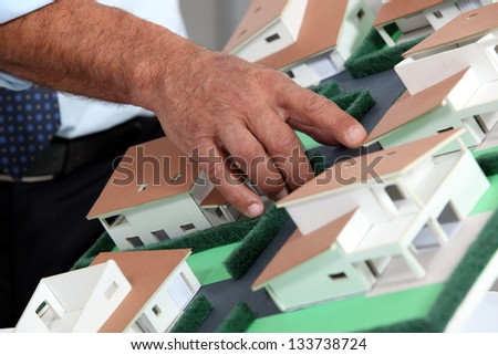 Man with a model of a housing estate - stock photo
