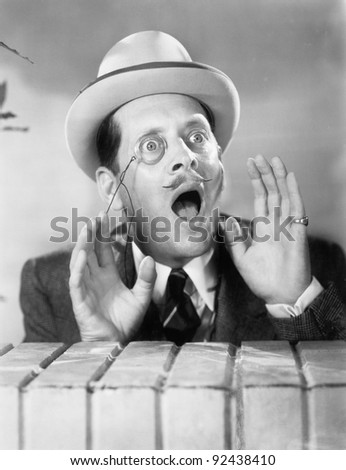 Man with a monocle looking surprised - stock photo