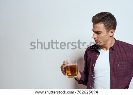man with a mug of beer on a light background, male alcoholism