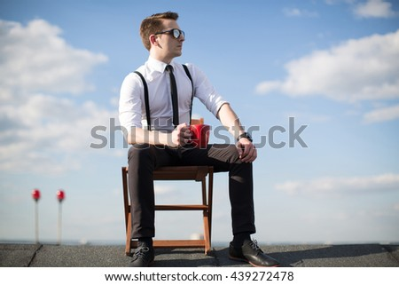 Man with a mug of coffee sitting on a chair