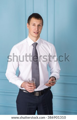man with a phone and a glass of water in hands - stock photo