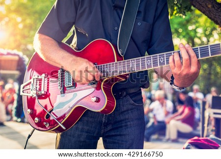 Man with a red electric guitar in the park playing a concert - stock photo