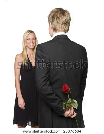 Man with a rose behind his back and a happy woman - stock photo