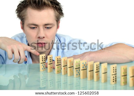Man with a row of dominoes - stock photo