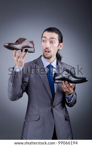 Man with a selection of shoes - stock photo