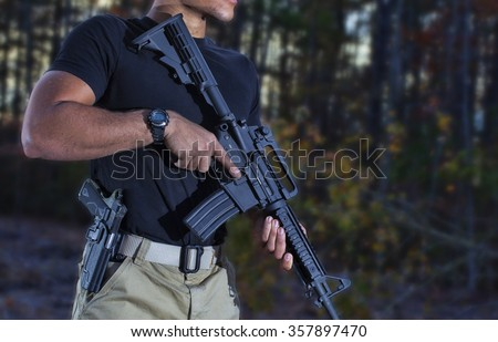 Man with a semi automatic rifle and handgun in the woods - stock photo