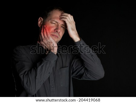 Man with a sick tooth keeps cheek hand. On a black background - stock photo
