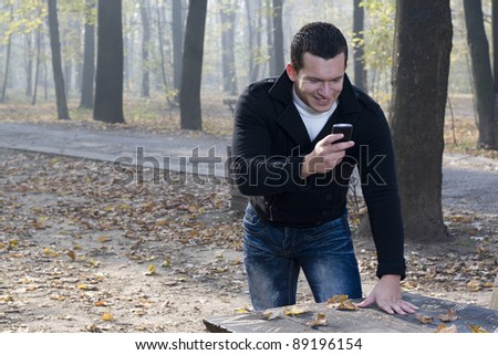man with a smile typing message in autumn park - stock photo