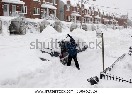 Man with a snow shovel. Car and street under snow. - stock photo