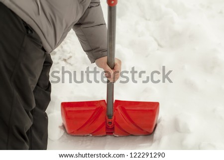 Man with a snow shovel near the snow pile - stock photo