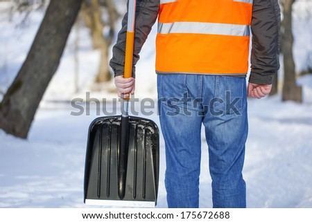 Man with a snow shovel on the sidewalk in winter - stock photo