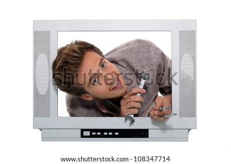Man with a spanner inside a television